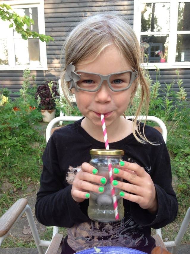 Flora when she had her glasses periode. Drinking glass with striped straw.